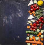 Confini i pomodori vegetariani di concetto dell'alimento sulle erbe del ramo della carota di un limone del cetriolo sul posto rus Fotografie Stock Libere da Diritti