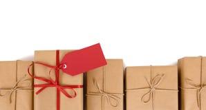 Confini la fila dei pacchetti della carta marrone, una unica con l'arco rosso del nastro e l'etichetta del regalo Fotografie Stock Libere da Diritti