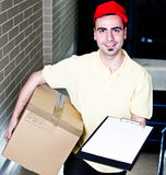 Confirm your delivery. Smiling young courier with package and blank clipboard Stock Photo