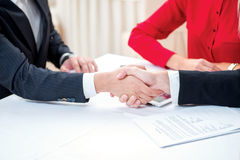 Confirmation of sponsorship. Three successful and confident busi. Nesspeople shake hands. Businesspeople in formal attire sitting in an office at a desk close-up Royalty Free Stock Photo
