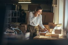 Confirming the order from customer. Woman online seller confirming orders from customer on the phone. E-commerce business owner looking at the papers and talking royalty free stock photo