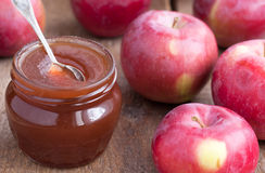 Confiserie d'Apple dans le pot en verre avec des pommes sur la table en bois Photo stock