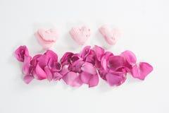Confiserie en forme de coeur et pétales de rose roses Photo stock