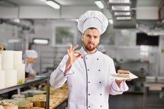 Confiseur avec un gâteau dans la boulangerie photographie stock libre de droits