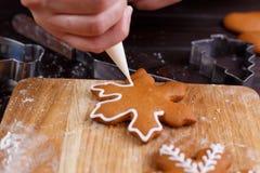 Confiseur décorant des biscuits de pain d'épice avec la confiserie i Photographie stock libre de droits