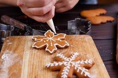 Confiseur décorant des biscuits de pain d'épice avec la confiserie i Image stock