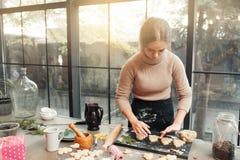 Confiseur féminin faisant cuire à la cuisine Images stock