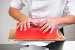 Confiseur professionnel composant le gâteau rouge délicieux, fin photo stock