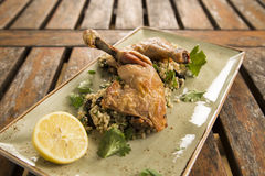 Confit Chicken with lemon, olive & herb cous cous Royalty Free Stock Photography