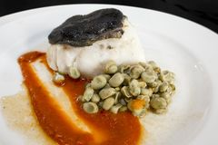 Confit of Cod Fillet, over Tomato Jam and Ali Oli of Black Garlic. With sautéed baby greens. Closeup stock photo