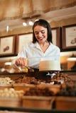 confitería Mujer que vende los caramelos de chocolate en tienda fotografía de archivo libre de regalías