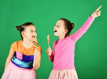 Confitería y concepto de la niñez Hermanas con alrededor y piruletas largas fotos de archivo libres de regalías