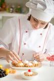 Confitero de sexo femenino profesional que adorna mini tartas de la fruta Foto de archivo libre de regalías