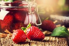 Confiture со всеми ягодами, винтажная деревянная предпосылка клубники кухонного стола, консервация лета варенья и варить, стоковое изображение