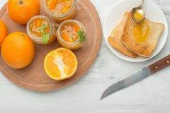 Confiture d'oranges dans un pot en verre sur un fond clair avec des pains grillés Avec l'espace vide pour l'inscription image libre de droits