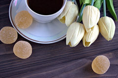 Confiture d'oranges et une tasse de café avec un bouquet des tulipes jaunes sur un fond en bois brun Pause de café photographie stock