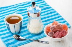 Confiture d'oranges rouge dans la cuvette, le sucre, le thé et la cuillère à café sur la serviette Photographie stock libre de droits