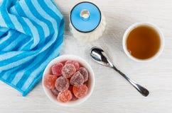 Confiture d'oranges rouge dans la cuvette, le sucre, le thé, la serviette et la cuillère à café Image libre de droits