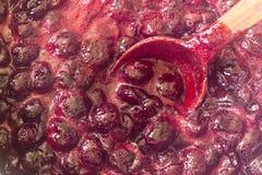 Confiture de cerise d'Ooking Remuez constamment avec les cerises rouge foncé de tourbillonnement d'une cuillère en bois et le suc photo libre de droits