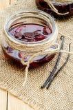 Confiture de fraise dans un pot en verre sur la toile à sac avec des cosses de vanille Image libre de droits
