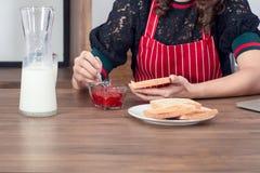 Confiture de fraise de diffusion de femme sur le pain grillé tout en prenant le petit déjeuner photos stock