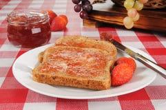 Confiture de fraise sur le pain grillé poussé de blé Photographie stock