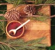 Confiture des cônes de pin sur une texture en bois avec des cônes de pin Photos stock