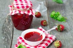 Confiture mit Erdbeeren und Basilikum auf einem hölzernen Hintergrund Lizenzfreies Stockfoto