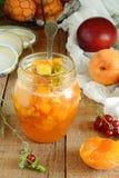 Confiture organique faite maison dans le pot en verre et les abricots et la nectarine mûrs sur la table rustique en bois images stock