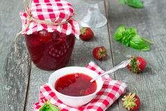 Confiture with strawberries and basil on a wooden background Royalty Free Stock Photo