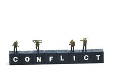 Conflict. Armed soldiers on the word conflict stock image