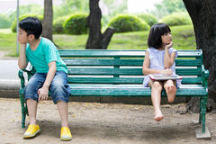 Conflict between the Asian brother and sister sitting on a woode Royalty Free Stock Image