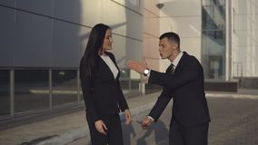Business people while working near office building. Conflict of businesspeople. Businessman and businesswoman in formal suits argue about something by swinging stock footage