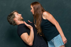 The conflict of couple. Women threatening and showing strength on dark background royalty free stock photo