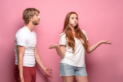 The conflict of couple. Women threatening and showing strength on pink background stock photography