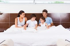 Conflict family lying in a bedcouple with children Royalty Free Stock Photography