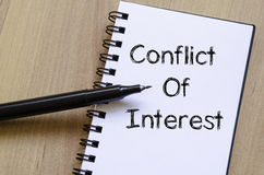 Conflict of interest write on notebook Stock Image