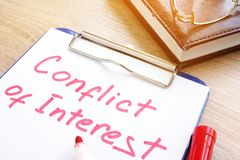 Conflict of interest written on a piece of paper. stock photo