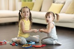 Conflict between little sisters. Kids are fighting, toddler girl takes toy, sibling relationships royalty free stock photo