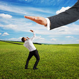Conflict between man and boss. Concept photo of conflict between subordinate and boss. frightened businessman looking up at big palm of his boss at outdoor Stock Photos