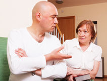 The conflict between mother and son. Son quarrel with mother, focus on man Stock Photos