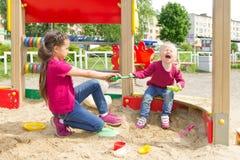 Conflict op de speelplaats Twee zusters die over een stuk speelgoed schop in de zandbak vechten stock foto's