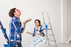 Conflict, redecoration and renovation concept - Young woman and man with annoying faces and bad emotions during. Conflict, redecoration and renovation concept royalty free stock photography