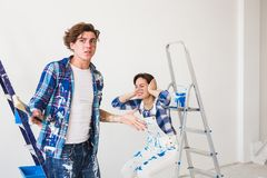 Conflict, redecoration and renovation concept - Young woman and man with annoying faces and bad emotions during. Conflict, redecoration and renovation concept royalty free stock image