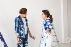 Conflict, repair and renovation concept - Young woman and man with annoying faces and bad emotions during renovation in. Conflict, repair and renovation concept stock images