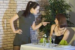 Conflict in restaurant. Conflict between two female friends in restaurant Stock Photo