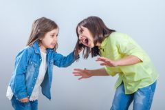Conflict between sisters, younger sister pulls the hair older si. Ster royalty free stock image