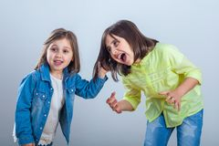 Conflict between sisters, younger sister pulls the hair older si. Ster stock photo