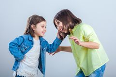 Conflict between sisters, younger sister pulls the hair older si. Ster stock photography
