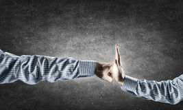 Conflict situation. Hand with open palm stopping angry clenched fist Royalty Free Stock Images